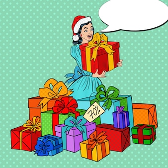 Pop art donna felice in cappello della santa con grandi scatole regalo sulla vendita di natale.
