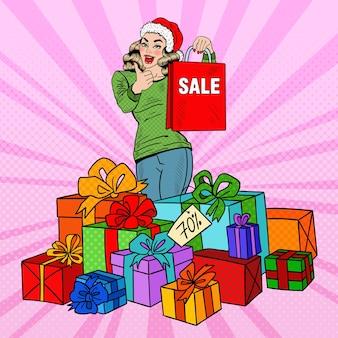 Donna felice di pop art in cappello della santa con la borsa della spesa e scatole regalo enormi sulla vendita di natale.