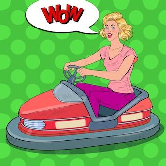 Pop art donna allegra equitazione paraurti auto alla fiera del divertimento. ragazza in auto elettrica al parco dei divertimenti.