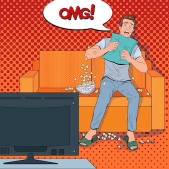 Pop art man guardando un film dell'orrore a casa. ragazzo scioccato guarda il film sul divano con popcorn.