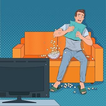 Pop art man guardando un film dell'orrore a casa. ragazzo terrorizzato guarda un film sul divano con popcorn.