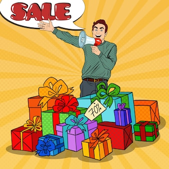 Uomo di pop art con il megafono che promuove la grande vendita in piedi in scatole regalo.