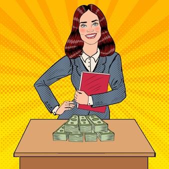 Pop art sorridente donna d'affari in piedi dietro il tavolo con i soldi.