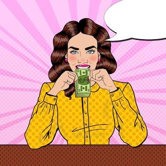Giovane bella donna di successo di pop art che mangia soldi.