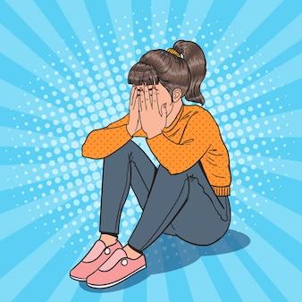 Pop art sconvolto giovane ragazza seduta sul pavimento. donna piangente depressa.