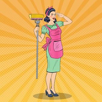 Pop art giovane donna casalinga fiduciosa che pulisce la casa con la scopa. illustrazione
