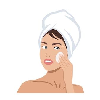 Ritratto di una bella donna con un asciugamano sulla testa che pulisce la cura della pelle del viso o il concetto di spa