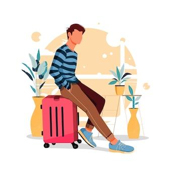 Ragazzo del ritratto che si siede sulla valigia in abiti alla moda