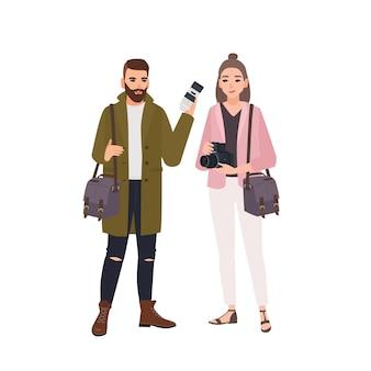 Ritratto di carino sorridente maschio e femmina fotografi isolati su sfondo bianco. coppia di fotogiornalisti professionisti con telecamere in piedi insieme. piatto del fumetto colorato illustrazione vettoriale.