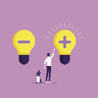 Uomo d'affari di pensiero positivo e negativo che sceglie la lampadina con il segno più