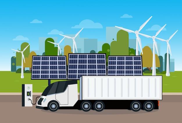 Centrale elettrica con il camion di rimorchio che si carica sopra le trombe di vento e le pile del pannello solare concetto ecologico del veicolo elettrico del carico di eco