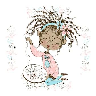 Una bella ragazza nera è impegnata nel ricamo e ricama un bellissimo motivo sul telaio.