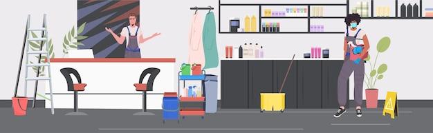 Pulitori professionisti coppia mix bidelli gara utilizzando attrezzature per la pulizia che lavorano insieme salone di bellezza interno orizzontale
