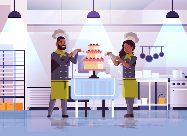 Coppia di pasticceri professionisti che decorano la gustosa torta di crema da sposa uomo afroamericano in uniforme cucina concetto di cibo interno moderno ristorante