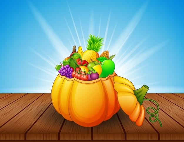 Cesto di zucca pieno di frutta e verdura sul tavolo di legno