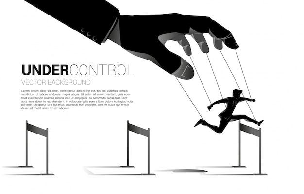 Padrone delle marionette che controlla silhouette di uomo d'affari correre e saltare attraverso ostacoli ostacolo. concetto di manipolazione e microgestione