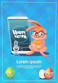 Lo smart phone delle cellule della tenuta del coniglio ha decorato la cartolina d'auguri di simboli di festa di pasqua delle uova variopinte