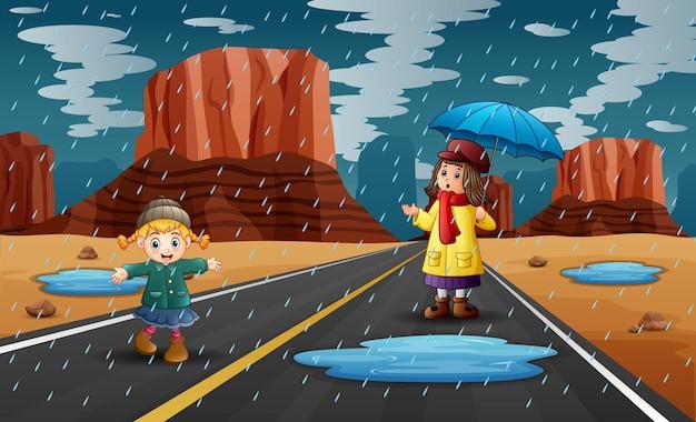 Stagione delle piogge con due ragazze che giocano sotto la pioggia