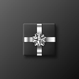 Scatola regalo nera realistica con fiocco metallico e nastro. illustrazione.