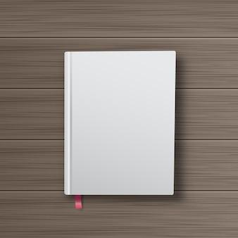 Libro realistico con copertina bianca su un tavolo di legno