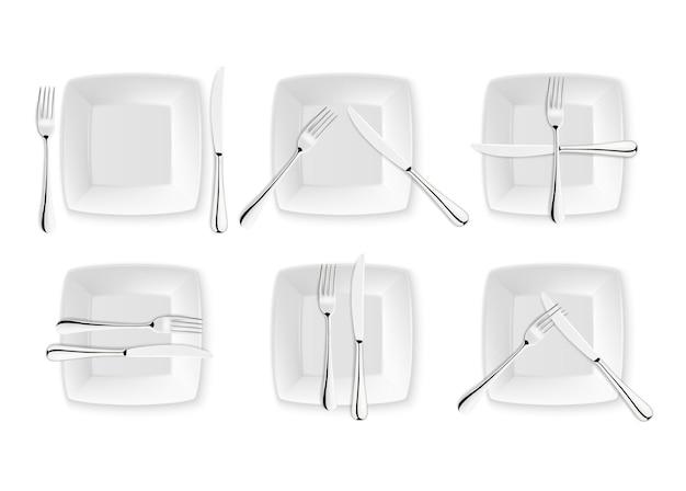 Posate realistiche e segni di etichetta da tavola, icone vettoriali isolate su sfondo bianco. set forchetta, coltello e piatto. modello di progettazione, mockup di stoviglie. vista dall'alto.
