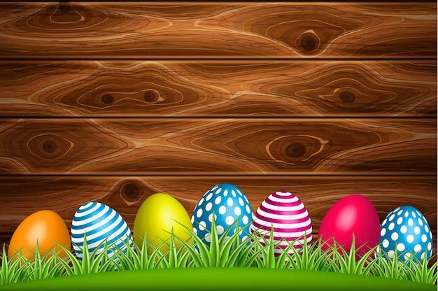 Uova di pasqua decorate realistiche sul campo di prato di erba verde su fondo di legno