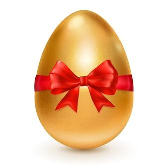 Uovo di pasqua dorato realistico legato con un nastro rosso con un grande fiocco rosso