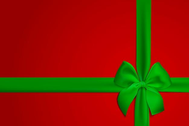 Fiocco verde realistico e nastro isolato su sfondo rosso modello per brochure o biglietto di auguri