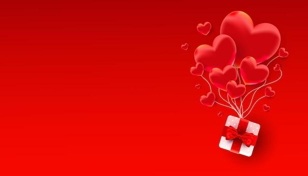 Realistici palloncini a forma di cuore decorano con un regalo a sorpresa