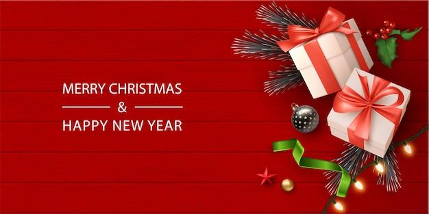Banner realistico di buon natale con confezione regalo e decorazioni natalizie