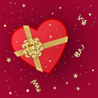 Una confezione regalo rossa realistica a forma di cuore decorata con un fiocco d'oro, vista dall'alto.
