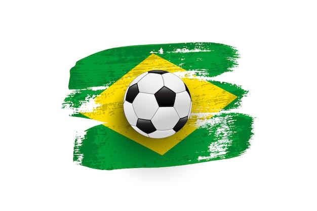 Pallone da calcio realistico sulla bandiera del brasile fatta di pennellate.
