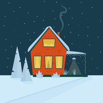 Una casa rossa accogliente con un tetto nella neve con alberi di natale in un cortile innevato