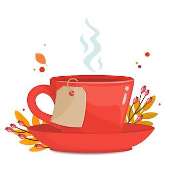 Tazza rossa con foglie autunnali, bacche e carta da tè.