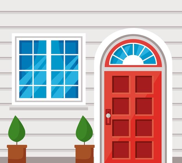 Finestra rossa della porta d'ingresso e piante della casa bianca