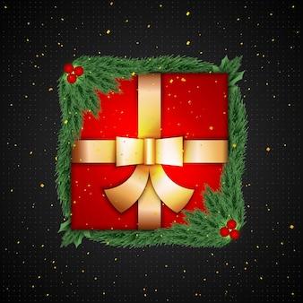 Confezione regalo rossa con foglie di pino intorno