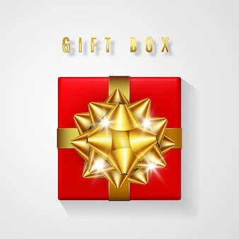 Confezione regalo rossa con fiocco dorato e vista dall'alto del nastro