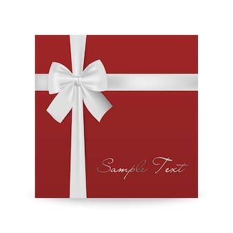 Biglietto di auguri rosso con fiocco bianco isolato su bianco