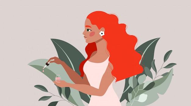 Olio rosso e pipetta della holding della ragazza dei capelli. bella signora in un morbido vestito rosa che mostra il prodotto di bellezza. foglie e rami di alberi tropicali. orecchino floreale.