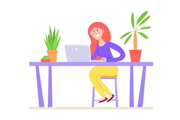 Donna dai capelli rossi che si siede con il computer portatile si siede al tavolo.