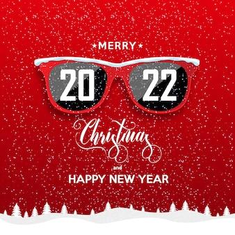 Occhiali hipster rossi su sfondo nevicata 2022 felice anno nuovo e buon natale paesaggio