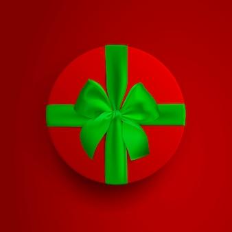 Scatola rotonda rossa con nastro verde e fiocco isolato su sfondo rosso vista dall'alto del coperchio della scatola