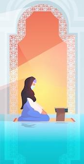 Donna musulmana religiosa che prega leggendo corano durante il concetto di religione di mese santo del ramare kareem