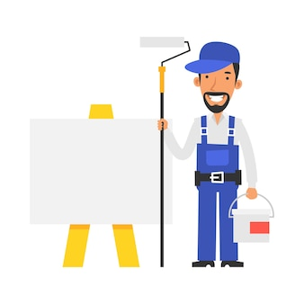 Il riparatore si trova vicino al cartello bianco e tiene in mano il rullo di vernice e la vernice del secchio e sorride