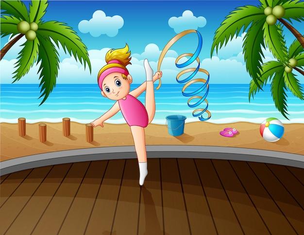 Ragazza relativa alla ginnastica ritmica con il nastro che gioca sulla spiaggia