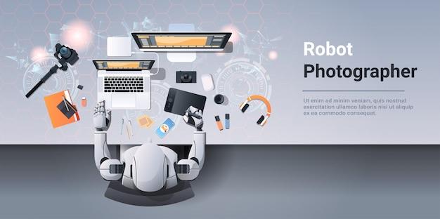 Fotografo robot seduto al posto di lavoro progettista robot