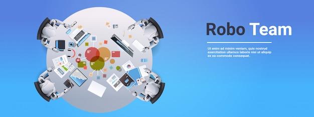 Riunione del gruppo robotico analizzando i robot di dati del grafico finanziario che lavorano ai computer seduti alla scrivania