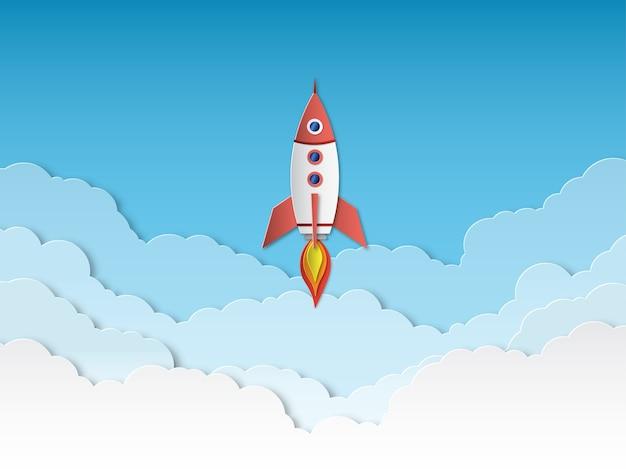 Carta tagliata a razzo. lancio di razzi con le nuvole, avvio di attività di successo.