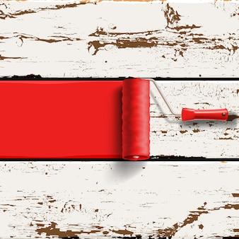 Spazzola a rullo con vernice rossa sul vecchio sfondo di pannelli in legno verniciato