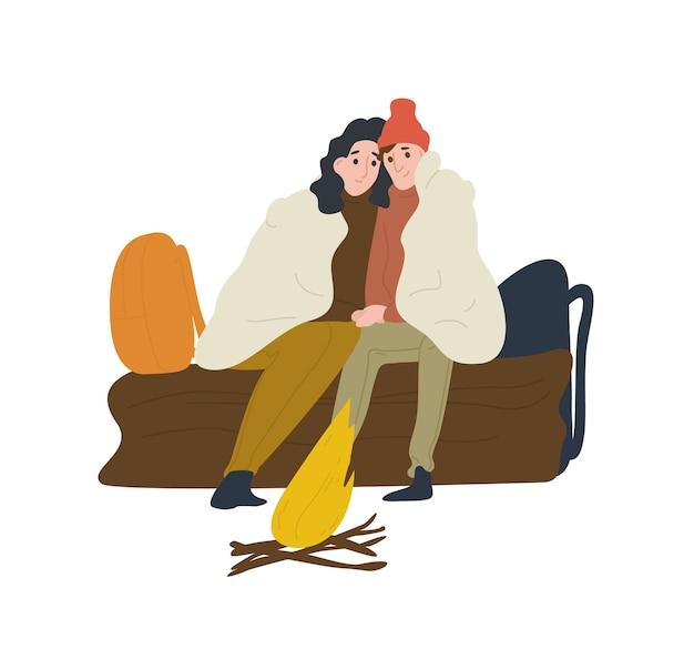 Coppie romantiche che si siedono sul registro e in fase di riscaldamento vicino al fuoco. fidanzato e fidanzata in viaggio in campeggio. turisti o viaggiatori con lo zaino in spalla in viaggi avventurosi